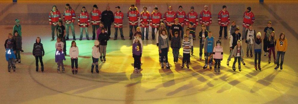Eishallen-Besucher bilden zusammen mit den PIRANHAS das WIRO-Logo auf der Eisfläche